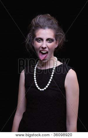 Beautiful Young Woman With Elegant Black Dress, With His Tongue Out, On Black Background, Studio Sho