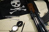 picture of ak47  - Pirates navigational tools and compass on a nautical navigation map along with an AK47 - JPG