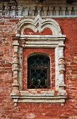 image of uglich  - Peeling brick wall of an ancient monastery and stucco window - JPG