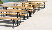 stock photo of nic  - wooden benches and tables in a row - JPG