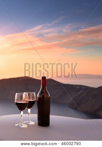 Wine bottle and glasses overlooking Santorini cliffs