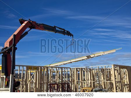 Crane loads trusses into place for new house