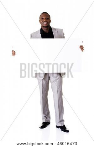 Happy successful businessman holding and showing blank advertisement. Isolated on white.