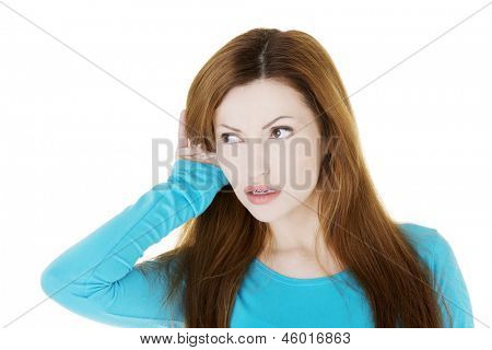 Surprised woman trying to listening a gossip , isolated on white