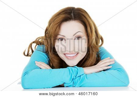 Pretty, happy, young woman in casual clothes sitting at the desk, isolated on white