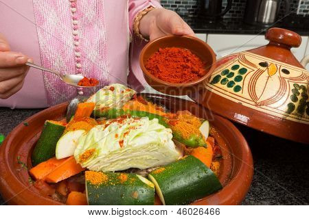 Traditional Moroccan immigrant woman in Europe adding spices to her tajine during Ramadan in her modern kitchen
