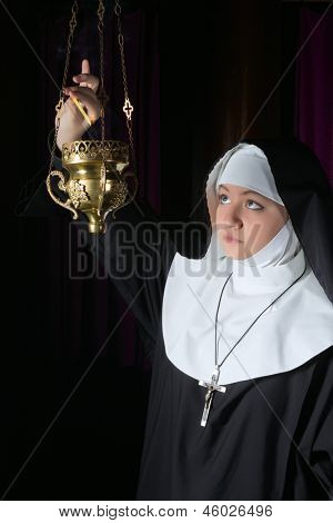 Nun in habit burning incense in a copper burner