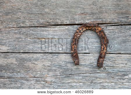 Old rustic horseshoe hanging on wooden wall to bring good fortune and luck