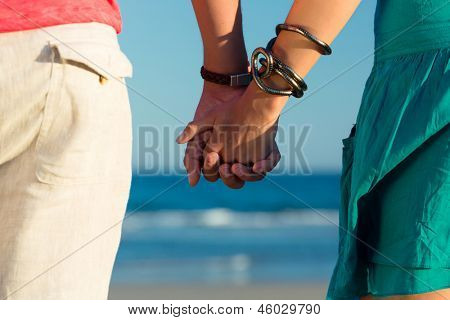 Man and woman, couple, enjoying the romantic sunset on a beach by the ocean in their vacation, they standing hand in hand, closeup
