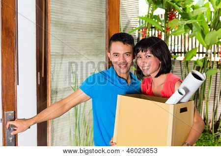 Real estate market - Young Indonesian couple moving in a home or apartment with a packing case or moving box