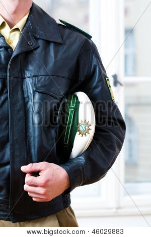 Police officer in police station, wearing his uniform with leather jacket and hat, he is ready for operation