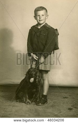 Vintage photo of little boy with a schoolbag and a dog (thirties)