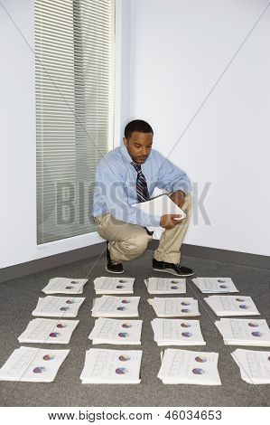 Young businessman collating reports