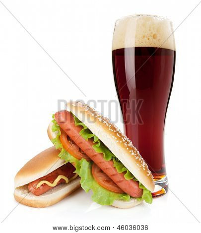 Dark beer glass and two hot dogs with various ingredients. Isolated on white background