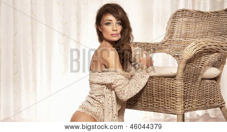 Sensual Brunette Beauty Sitting In Bright Room, Looking At Camera.