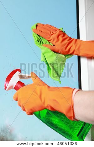 Gloved Hand Cleaning Window Rag And Spray