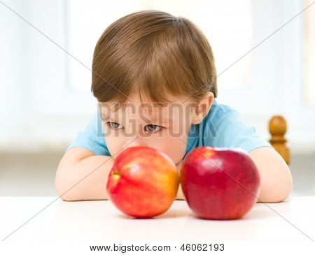 Portrait of a sad little boy with red apples