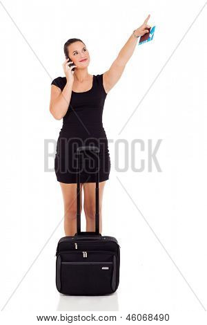 female business traveler pointing up and talking on cell phone over white background