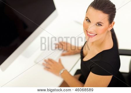 overhead view of cheerful businesswoman working on a modern computer