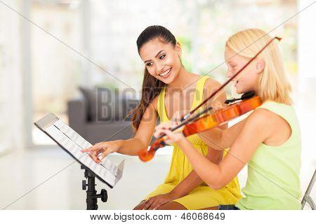 preteen girl play violin under music teacher's instructions
