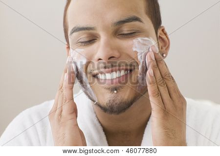 Young man applying shaving cream on his cheeks