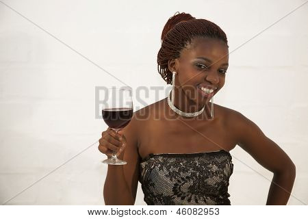 Beautiful Young African Woman Holding A Glass Of Red Wine