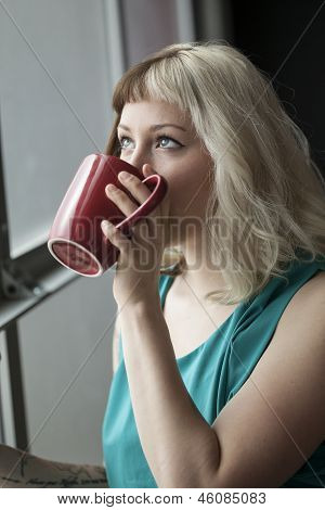 Beautiful Young Woman Drinking From Red Coffee Cup
