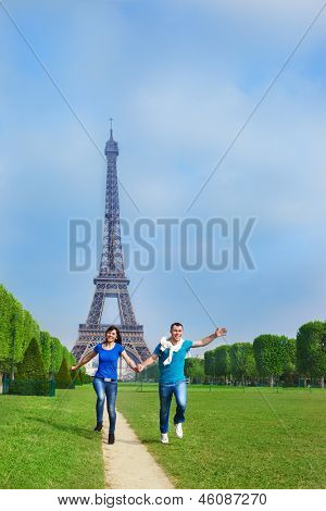 Happy young man and woman running along the Champ de Mars in Paris, France