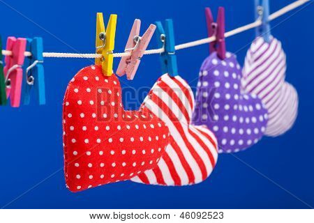 Hearts Hanging On A Clothesline With Clothespins, Focus On Red. Blue Background