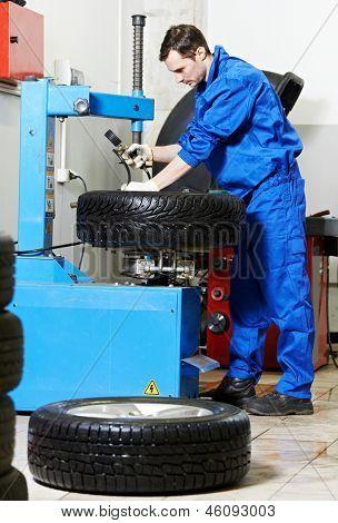 mechanic repairman installing automobile car wheel on tyre changers