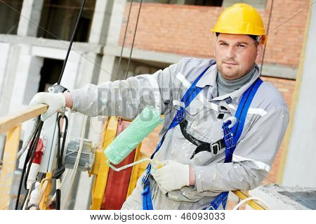 builder worker painting facade of building with roller