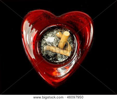 Cigarette butts in a heart shaped ashtray