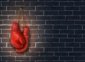 stock photo of boxing  - Stop competing and putting an end to business competition by hanging up a pair of red boxing gloves on a dark rustic old brick wall as a concept of stopping the fight to find the cure - JPG