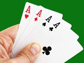 stock photo of ace spades  - Man hand holding four aces on green background with clipping path - JPG