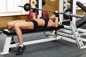 stock photo of barbell  - Sports young woman doing exercises with barbell on bench in the gym - JPG