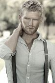 stock photo of suspenders  - Outdoor portrait of a handsome young confident man - JPG
