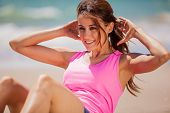 image of outfits  - Gorgeous young brunette in sporty outfit exercising at the beach - JPG