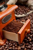 stock photo of wooden box from coffee mill  - coffee grinder and sack with coffee beans close up - JPG