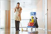 stock photo of broom  - Adult cleaner maid woman with mop and uniform cleaning corridor pass or hall floor of business building - JPG
