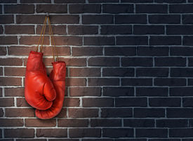 picture of stop fighting  - Stop competing and putting an end to business competition by hanging up a pair of red boxing gloves on a dark rustic old brick wall as a concept of stopping the fight to find the cure - JPG