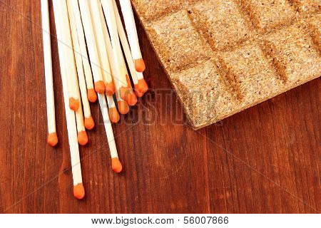 Long matches and dry fuel, on wooden background