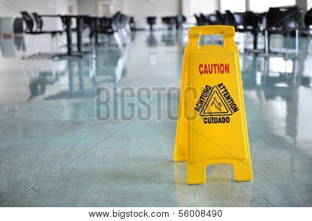Caution yellow sign inside building hallway
