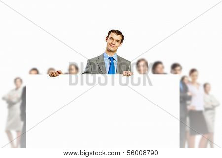Image of young man holding blank banner with crowd of business people at background