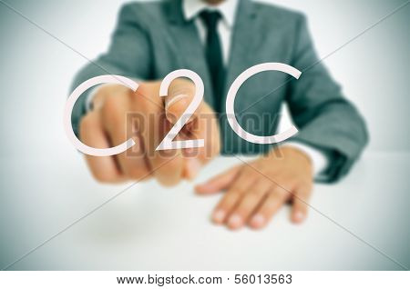 man wearing a suit sitting in a table pointing to the word C2C, consumer-to-consumer, written in the foreground