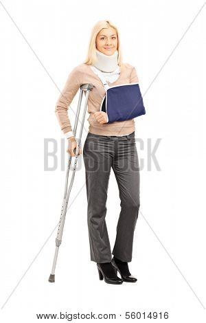 Full length portrait of a happy blond female with broken arm holding a crutch posing isolated on white background