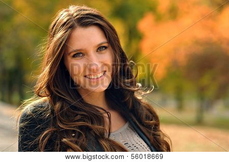 Portrait of smiling brunette girl a autumnal park