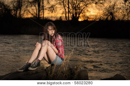 Girl Sitting On A River Rock