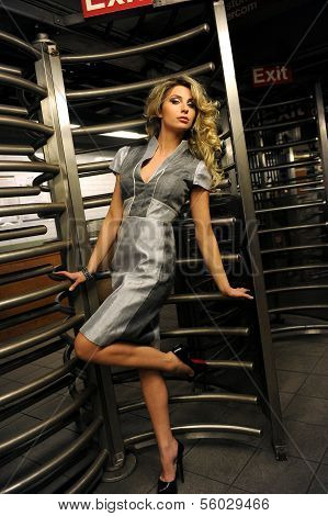 Fashion model standing by entrance with revolving door