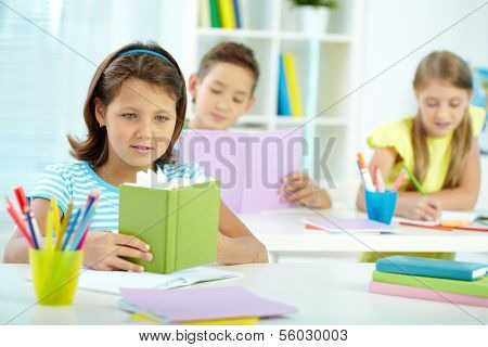 Portrait of lovely girl looking in notepad with her two schoolmates on background