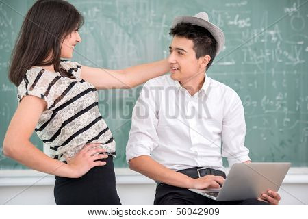 Highschool boy with laptop talking to his female classmate